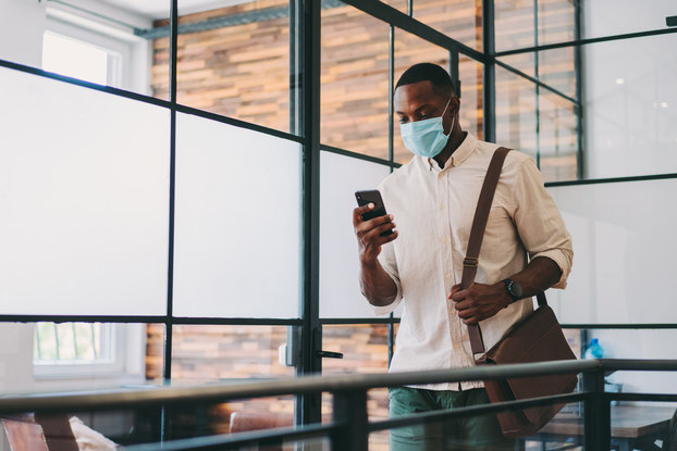 Man walking through office wearing a mask and looking at his phone.
