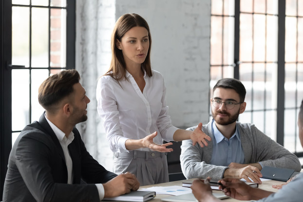 Businesswoman speaks to group in modern conference room