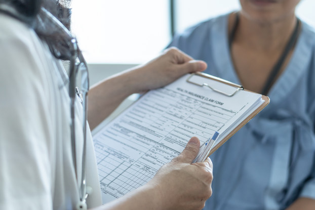 A shot from the neck down showing a person holding a form on a clipboard and a pen and another person wearing medical scrubs.