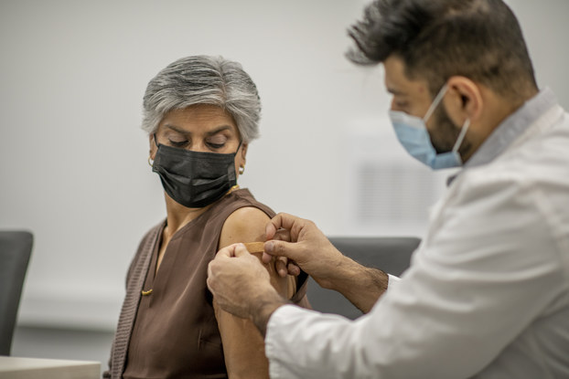 A doctor puts a band aid on a woman's arm after administering the COVID-19 vaccine injection.