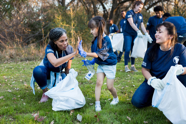 People in dark blue shirts pick up trash in a grassy field. In the background, against a forest backdrop, participants hold open white trash bags. In the foreground, a little girl high-fives a woman holding a trash bag. Another woman, at right, watches the high-five and swallows.