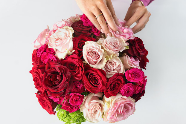 Top view of a person's hands putting together a floral arrangement from Bouquet Box.