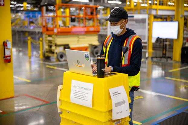 Amazon associate working inside the warehouse wearing PPE.