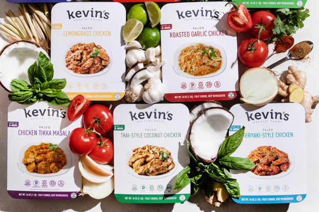 Display of Kevin's Natural Foods meals surrounded by fresh vegetables.