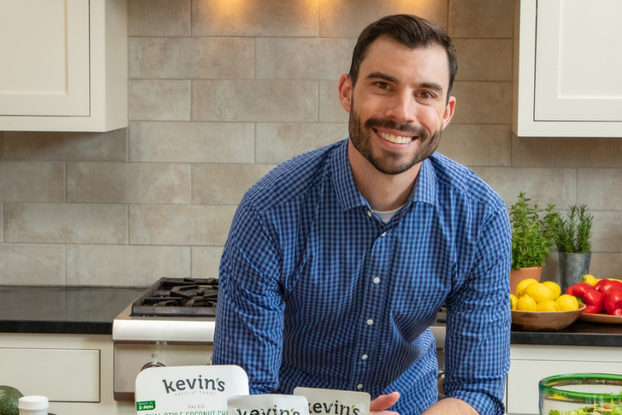 Kevin McCray, founder of Kevin's Natural Foods, in kitchen with a display of meals and seasonings.