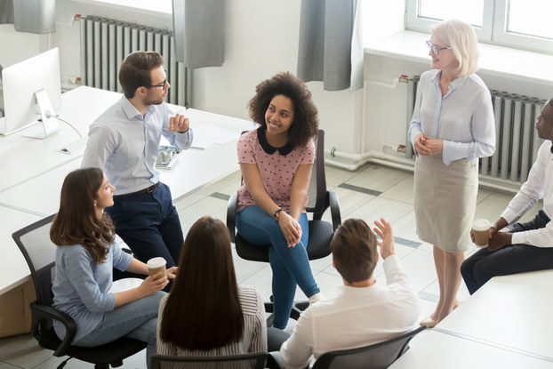 Employee group actively in discussion at office meeting.