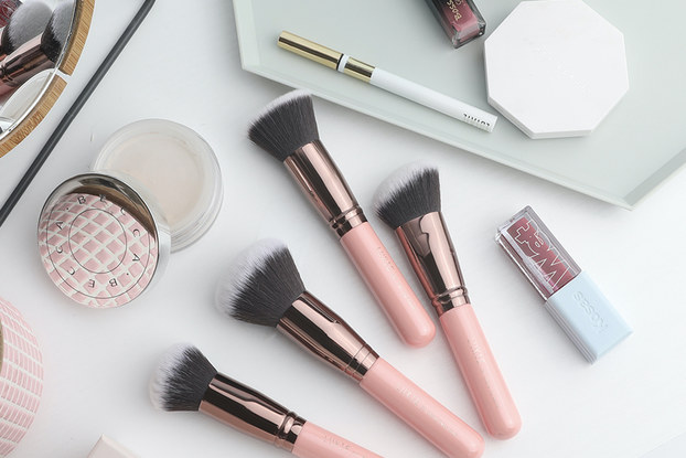 Luxie's beauty products and brushes displayed on a white surface.