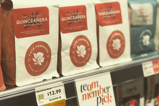 Bags of coffee by Cafe Femenino on a grocery store shelf.