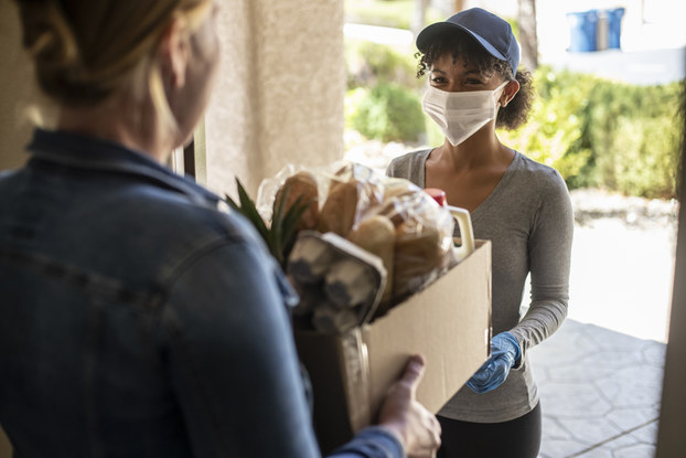 Woman delivering groceries to a customer.