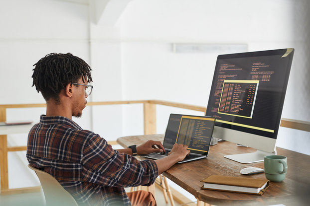 Computer programmer working on a laptop with an extra monitor.