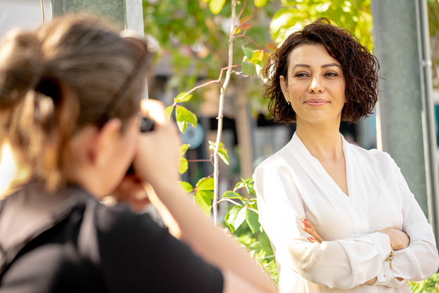 Professional adult getting headshot taken by a photographer outside.