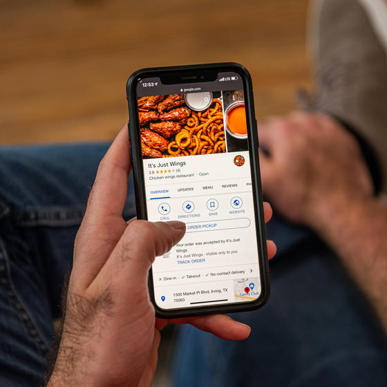 Person holding phone ordering It's Just Wings through a food delivery app.