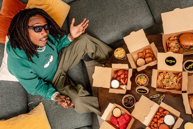 Wiz Khalifa posing with takeout boxes of food from HotBox by Wiz Khalifa.