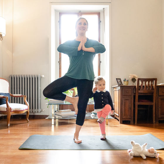 Woman doing yoga with her daughter.
