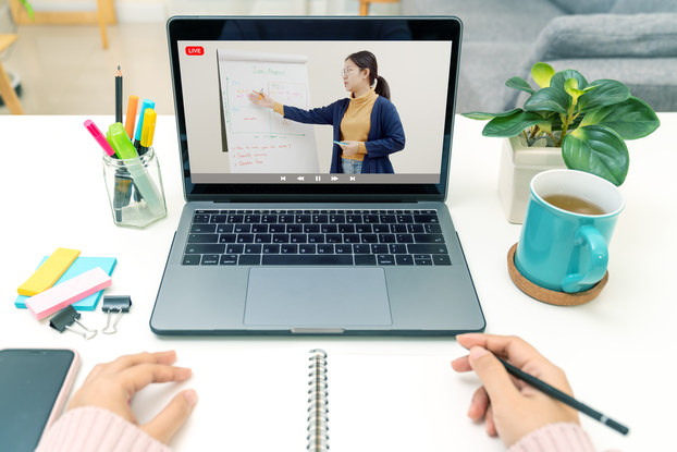 A POV shot of someone watching a class on a laptop and taking notes in a notebook. The laptop screen shows a woman gesturing to an easel displaying a large pad of paper covered with notes.