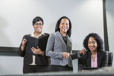 A trio of Black women wearing business attire faces the camera. The women are smiling. The woman standing on the left is holding an open binder and the one sitting on the right is holding an electronic tablet.