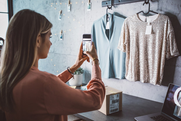Small business owner taking photos of clothing for an online store.