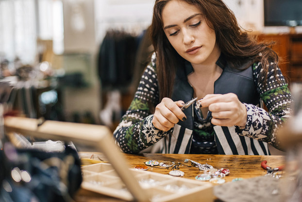 A woman sits at a table and uses a set of pliers to adjust a small piece of jewelry. Other pieces of jewelry -- namely pendants with various designs -- lay on the table before her, along with an open wooden box with several small compartments.