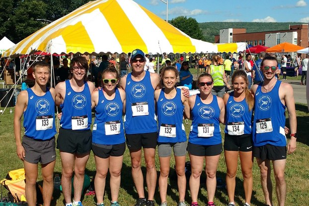 Running race participants pose outdoors with race bibs