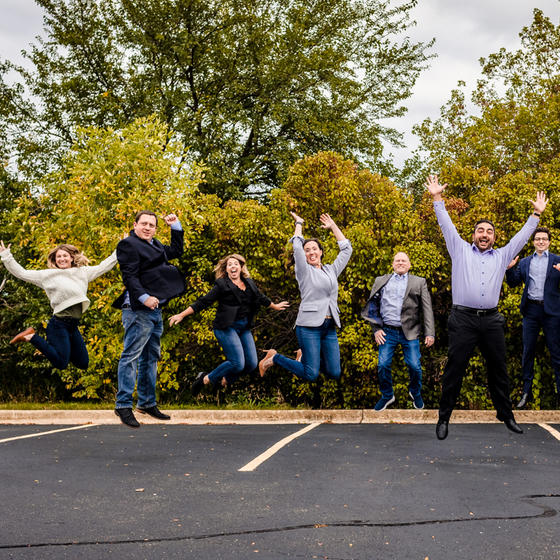 Business people pose happily in a parking lot