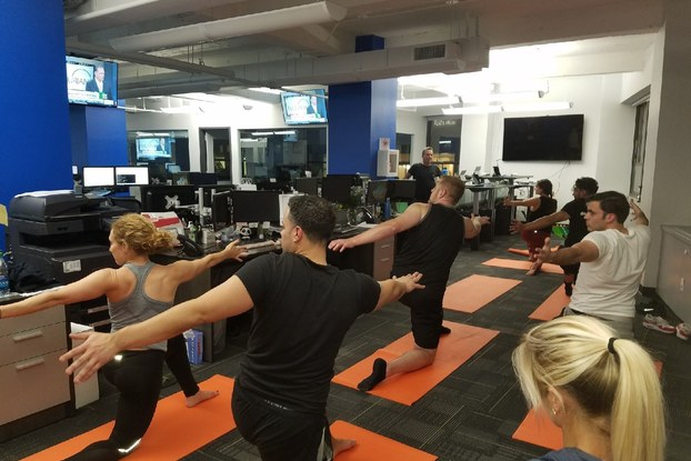Coworkers participate in group yoga class in modern office