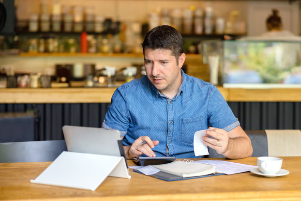 A man sits at a wooden counter and types on a calculator while looking at the screen of a tablet. In one hand, he holds a receipt and a folder of papers sits on the counter in front of him.