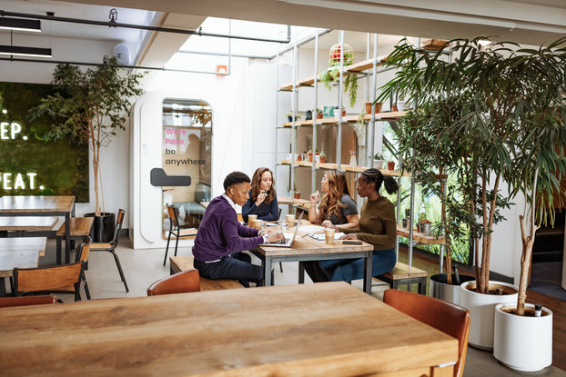 Team of employees at a table inside a trendy, modern office space.