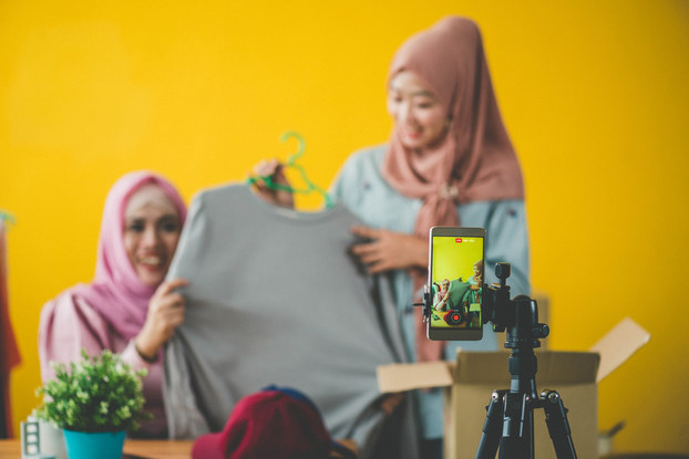 Two women modeling clothing for a video being recorded on a smartphone.