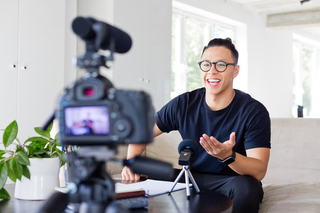 A male vlogger sits on the edge of a couch and speaks to a camera. The camera, which has a microphone attachment on top of it, stands on a tripod in the foreground, out of focus.