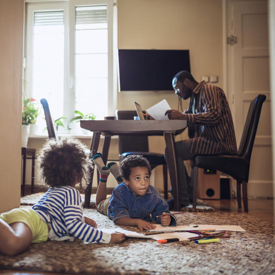 Father working from home while kids play on the floor.