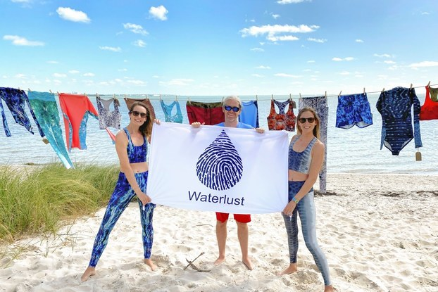 The employee team at Waterlust holding a business sign on the beach.