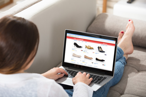 An over-the-shoulder shot of a woman browsing an online shoe store on her laptop. She reclines on a couch with her legs stretched out in front of her. Her feet are bare and her toenails are painted red.