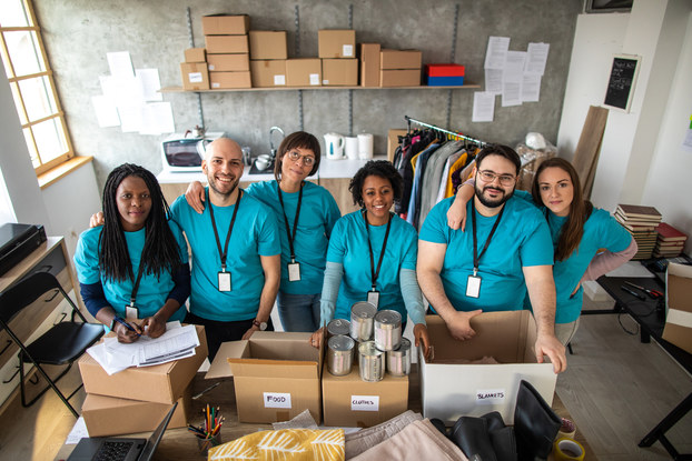 """A diverse group of six people stands in a row behind a table piled with boxes of donations marked """"food"""" and """"clothes."""" The group members all wear turquoise t-shirts and white cards on black lanyards. The room around them is plain and industrial and filled with racks of clothing, stacks of books, more boxes and assorted office furniture."""