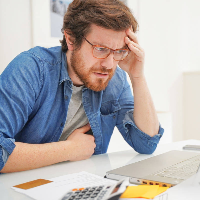 A man looks at his laptop with one hand on his head. His face is worried. Beside the laptop are some papers and a calculator.