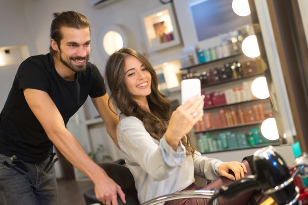 A woman uses her smartphone to take a selfie of herself and her hair stylist. The woman sits in the styling chair and has slightly wavy brown hair. The stylist behind her wears a black t-shirt and has hair clips clipped to the pockets of his jeans. He has a beard and a small man bun. In the background are several shelves of hair products sorted by color.