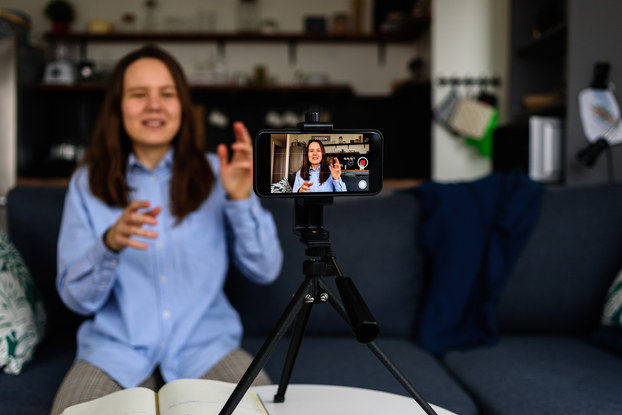 A smartphone positioned horizontally on a tripod films a woman speaking and gesturing. In the background, out of focus, is the woman herself.