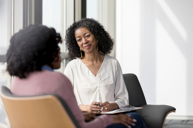 Mature counselor listens compassionately to client