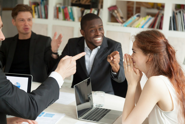 Employees happily celebrate colleague's achievement who appears shy.
