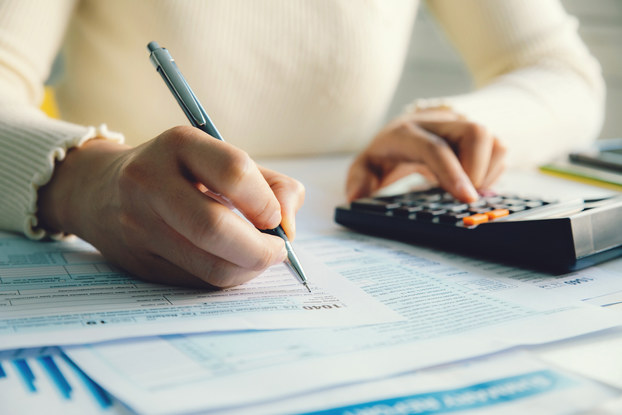 Close-up on a pair of hands. One hand uses a mechanical pencil to fill out a form while the other presses buttons on a calculator.