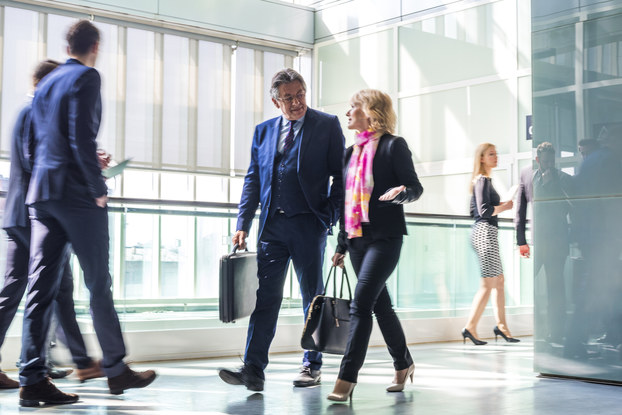 A pair of businesspeople walks through a hallway in a brightly lit modern building. Several other businesspeople are in motion around them. In the background are floor-to-ceiling, wall-to-wall glass windows.