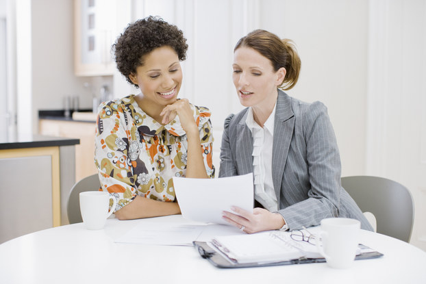 Businesswoman reviews paperwork with woman.