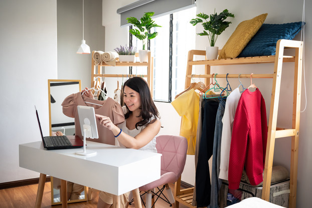Woman doing a livestreamed video selling clothing.
