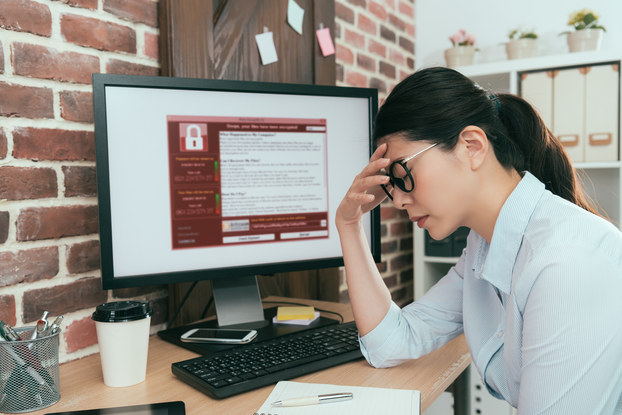 A woman sits at a desk with one hand to her forehead and her eyes closed. She looks defeated. The computer monitor on her desk displays a red and white window filled with text. An icon of a closed padlock suggests that the computer is locked.