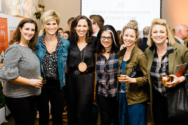 Smiling women pose at corporate event