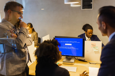 A group of people seen through a window, with reflections of lights laying over the scene. Three worried colleagues cluster around a computer showing a blue error screen. In the background, two other people work at their own computers.