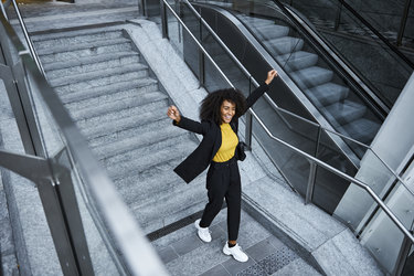 Woman leaving work happily smiling and raising her arms in the air.