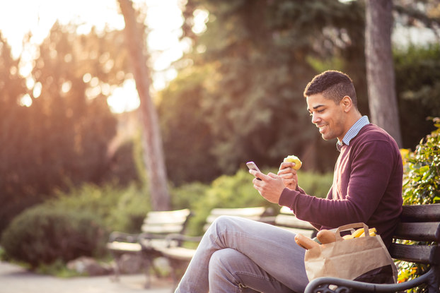 Man eating a snack while checking his phone in a park