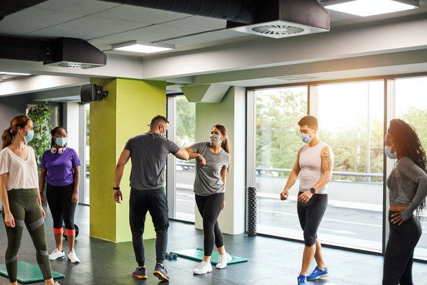 People exercising in a fitness studio with masks on.