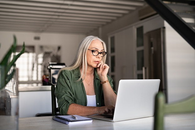 A woman in a minimalist room sits at a table and looks at a laptop. One hand is on her chin and she looks thoughtful.