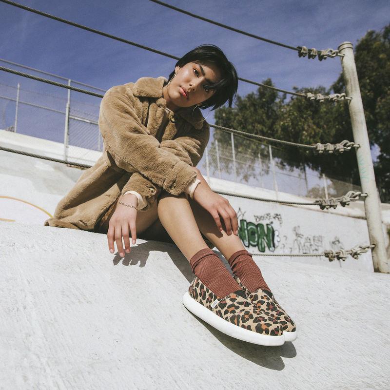 Model wearing Toms leopard shoes.